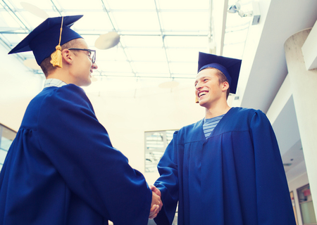 education, graduation and people concept - smiling students in mortarboards and gowns shaking hands outdoors Stock Photo