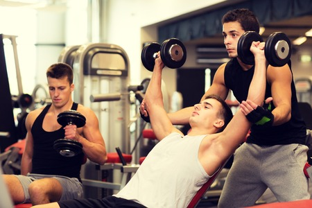 strength training: sport, fitness, lifestyle and people concept - group of men with dumbbells in gym Stock Photo