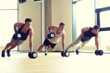 deporte, fitness, estilo de vida y concepto de la gente - grupo de hombres con pesas en el gimnasio