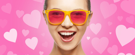 teen love: love, happiness and valentines day concept - amazed teen girl in pink sunglasses on background with hearts