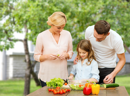 vegetarian food, culinary, happiness and people concept - happy family cooking vegetable salad for dinner over house and summer garden background Imagens