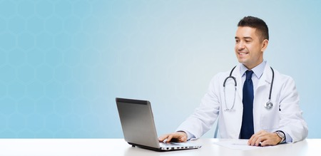 white coat: medicine, profession, technology and people concept - smiling male doctor sitting at table with laptop and stethoscope over blue background
