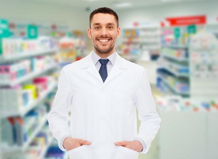 medicina, farmacia, la gente, la atención médica y el concepto de la farmacología - sonriendo farmacéutico de sexo masculino en la capa blanca sobre fondo droguería