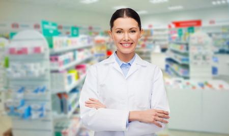 medicina, farmacia, la gente, la atención médica y el concepto de la farmacología - feliz mujer joven sobre el fondo farmacéutico farmacia