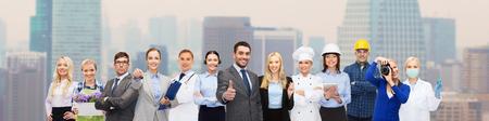 profesiones: personas, profesión, calificación, el empleo y el concepto de éxito - hombre de negocios feliz sobre los trabajadores profesionales que muestran los pulgares arriba sobre el fondo de la ciudad Foto de archivo