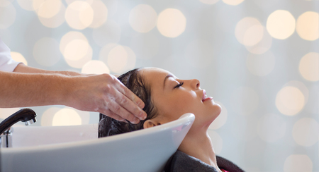 woman washing hair: beauty salon, hair care and people concept - hairdresser hands washing happy young woman head over holidays lights background