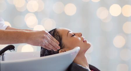 salón de belleza, cuidado del cabello y la gente concepto - las manos del peluquero que lavan la cabeza feliz mujer joven durante las vacaciones luces de fondo