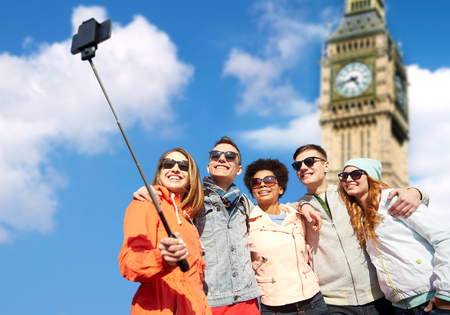 tourism, travel, people, leisure and technology concept - group of smiling teenage friends taking selfie with smartphone and monopod over london big ben tower background Фото со стока