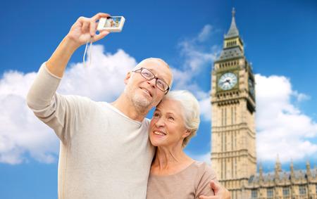 la edad, el turismo, los viajes, la tecnología y el concepto de la gente - pareja de alto nivel con la cámara que toma autofoto sobre la torre Big Ben en el fondo de la ciudad de Londres