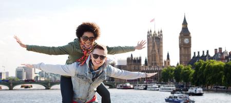 友情、レジャー、国際、自由および人々 のコンセプト - ロンドン背景の国会議事堂、テムズ川の川の家で楽しい色合いで幸せな 10 代のカップル 写真素材