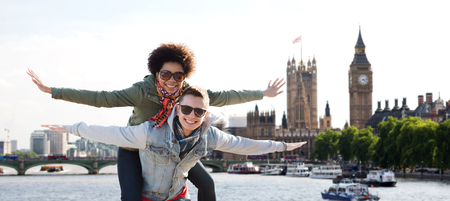 friendship, leisure, international, freedom and people concept - happy teenage couple in shades having fun over houses of parliament and thames river in london background