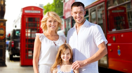 kingdom: summer holidays, travel, tourism and people concept - happy family over london city street background Stock Photo