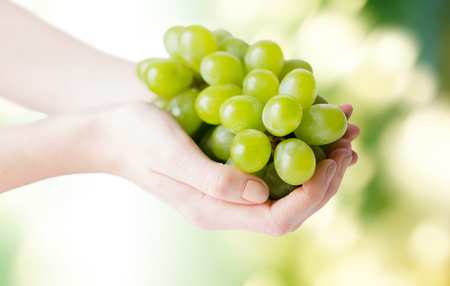 bunch of: healthy eating, diet, organic food and people concept - close up of woman hands holding green grape bunch over natural background