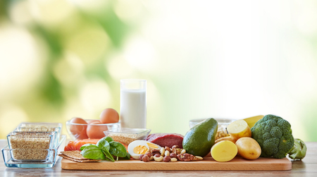 nutrition: balanced diet, cooking, culinary and food concept - close up of vegetables, fruits and meat on wooden table over green natural background