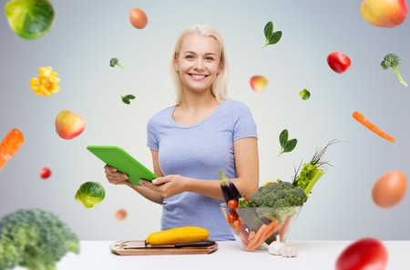 over eating: healthy eating, cooking, vegetarian food, technology and people concept - smiling young woman with tablet pc computer and bowl of vegetables over gray background with falling vegetables