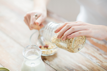 food concept: food, healthy eating, people and diet concept - close up of woman eating muesli with milk for breakfast Stock Photo