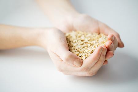 avena: alimentación saludable, la dieta, la alimentación vegetariana y concepto de la gente - cerca de la mujer con las manos copos de avena en casa