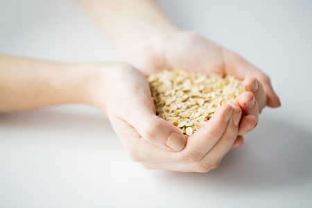 oats: healthy eating, dieting, vegetarian food and people concept - close up of woman hands holding oatmeal flakes at home Stock Photo