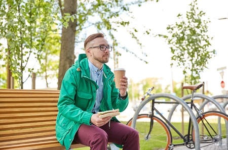 food and drinks: people, style, leisure and lifestyle - happy young hipster man with coffee cup and sandwich eating and drinking on city street