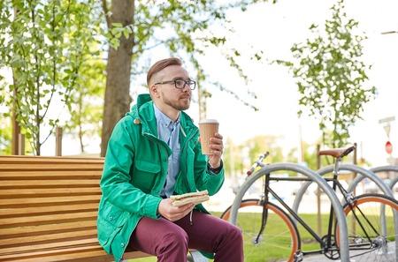 alimentos y bebidas: personas, estilo, ocio y estilo de vida - hombre inconformista joven feliz con la taza de caf� y comer s�ndwich y beber en la calle de la ciudad