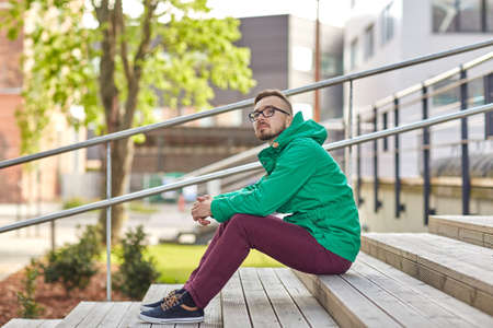 modern buildings: people, style, leisure and lifestyle - happy young hipster man in eyeglasses and jacket sitting on stairs in city Stock Photo