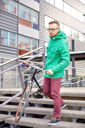 bajando escaleras: people, sport, style, leisure and lifestyle - young hipster man carrying fixed gear bike down stairs in city Foto de archivo