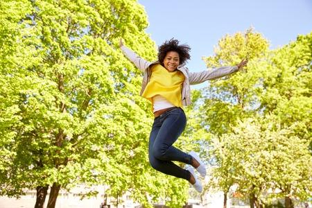jumping: la gente, la raza, el origen étnico y el concepto de retrato - mujer joven afroamericano feliz en el parque de verano