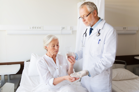 doctor giving glass: medicine, age, health care and people concept - doctor giving medication and water to senior woman at hospital ward