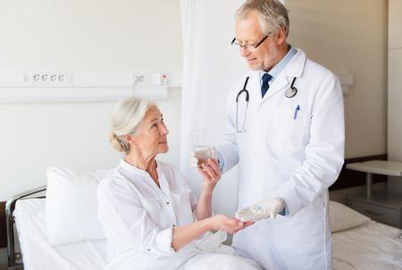 la medicina, l'età, l'assistenza sanitaria e la gente concetto - medico, che danno i farmaci e acqua alla donna maggiore al reparto ospedaliero