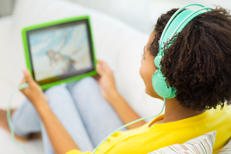 to browse: people, technology and leisure concept - close up of happy african american young woman lying with tablet pc computer and headphones listening to music and watching video at home Stock Photo