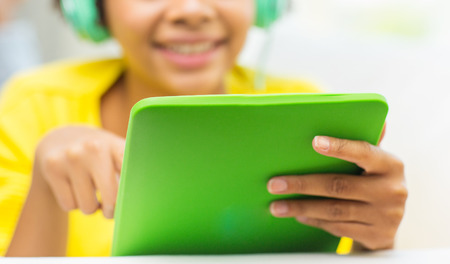 people, technology and leisure concept - close up of happy african american young woman lying with tablet pc computer and headphones listening to music at home Stock fotó