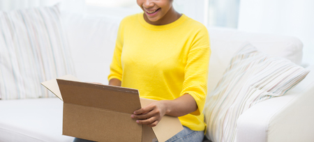 people, delivery, shipping and postal service concept - happy african american young woman opening cardboard box or parcel at home Stock Photo