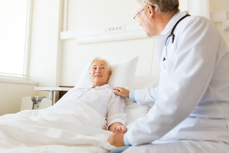 medicine, age, support, health care and people concept - doctor visiting and cheering senior woman lying in bed at hospital ward Stockfoto