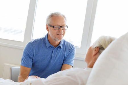 old man happy: medicine, age, support, health care and people concept - happy senior man visiting and cheering his woman lying in bed at hospital ward Stock Photo