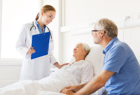 doctor care: medicine, age, health care and people concept - senior woman, man and doctor with clipboard at hospital ward Stock Photo