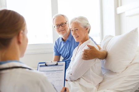 sick person: medicine, age, health care and people concept - senior woman, man and doctor with clipboard at hospital ward Stock Photo