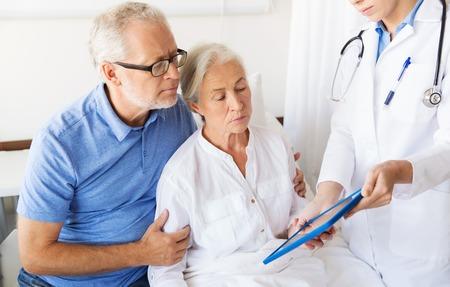 la medicina, la edad, la salud y las personas concepto - mujer mayor, el hombre y el médico con el ordenador Tablet PC en la sala del hospital Foto de archivo