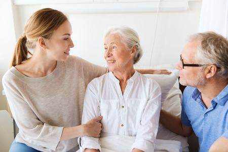 elderly: medicine, support, family health care and people concept - happy senior man and young woman visiting and cheering her grandmother lying in bed at hospital ward Stock Photo