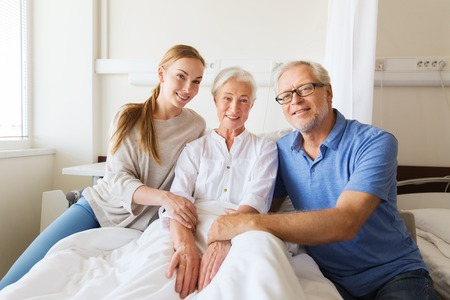 medicine, support, family health care and people concept - happy senior man and young woman visiting and cheering her grandmother lying in bed at hospital ward Archivio Fotografico