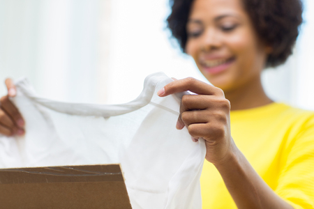 parcel: people, delivery, commerce, shipping and postal service concept - close up of happy african american young woman taking clothes out of cardboard box or parcel at home