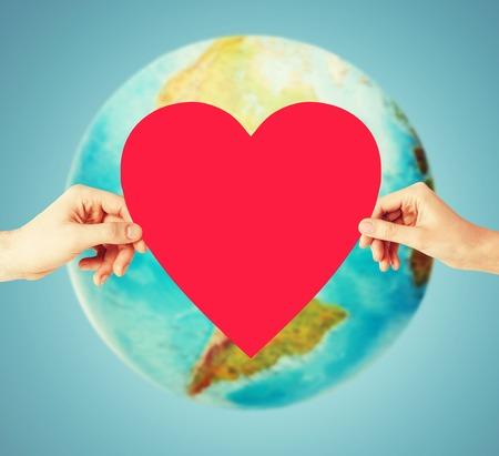 simbolo uomo donna: persone, l'amore, la salute, l'ambiente e la carità concetto - stretta di mani di donna che tiene cuore rosso sopra terra globo e sfondo blu