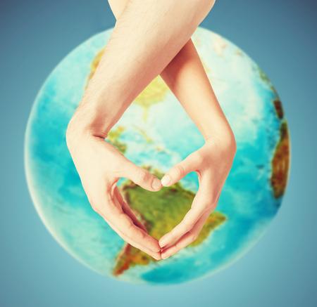 mensen, vrede, liefde, het leven en het milieu concept - close-up van menselijke handen waaruit blijkt hartvorm gebaar over de aarde wereldbol en blauwe achtergrond Stockfoto