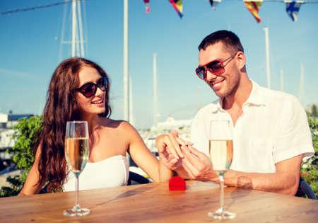 anillo de boda: amor, el fechar, las personas y las vacaciones de concepto - sonrientes par de gafas de sol con champán y pequeña caja de regalo de color rojo que pone el anillo de bodas en el dedo en el café