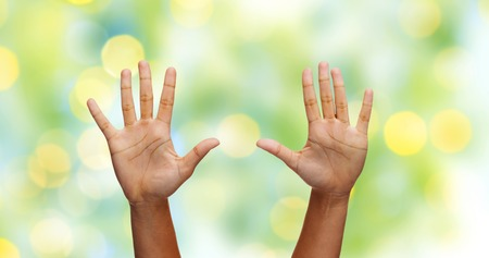 two hands: gesture, people and body parts concept - african woman two hands showing palms or making high five over green lights background