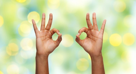 gebaar, people and body parts concept - Afrikaanse vrouw twee handen die ok teken over de blauwe lucht en wolken achtergrond