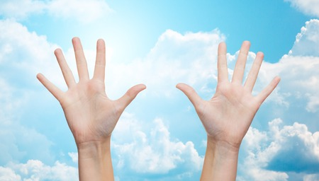 clouds making: gesture, people, and body parts concept - two woman hands showing palms or making high five over blue sky and clouds background