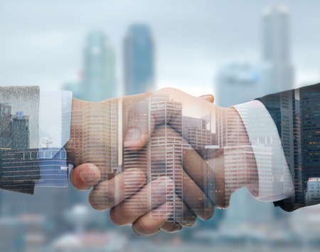stretta di mano: affari, partenariato, collaborazione e il concetto gesto - uomo d'affari e imprenditrice agitando le mani sulla città di doppio fondo di esposizione