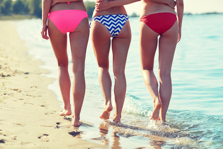 bikini butt: summer holidays, travel, body care and people concept - close up of happy young women walking and hugging on beach from back