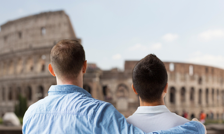 homosexual sex: people, homosexuality, same-sex marriage, travel and love concept - close up of happy male gay couple hugging from back over coliseum in rome background Stock Photo