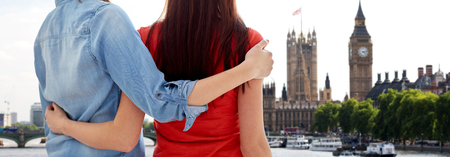 britain: people, homosexuality, same-sex marriage, travel and gay love concept - close up of happy lesbian couple hugging over big ben and houses of parliament in london background